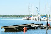 stock photo of marina  - Small bridge without boats and larger marina with boats in distance - JPG