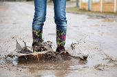stock photo of woman boots  - Woman with rain boots jumps into a puddle - JPG