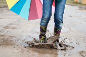 image of woman boots  - Woman with rain boots jumps into a puddle - JPG