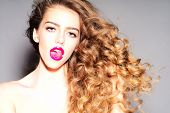 stock photo of tongue licking  - Amazing sexy young girl with curly hair licking her bright pink lips with tongue looking forward standing on grey background horizontal picture - JPG