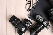 picture of megapixel  - Modern cameras with glasses and notebook on wooden table - JPG