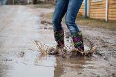 pic of woman boots  - Woman with rain boots jumps into a puddle - JPG