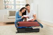 pic of boarding pass  - Portrait Of Happy Young Couple Packing Luggage Showing Boarding Pass - JPG