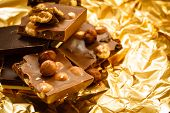 stock photo of hazelnut  - Closeup different sorts chocolate pieces and hazelnuts - JPG