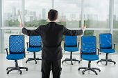 stock photo of conduction  - Businessman conducting his invisible employees - JPG