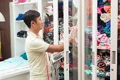 picture of wardrobe  - Asian man tailor choose fabric fashion clothes wardrobe dress designer using tablet  - JPG