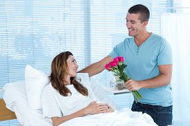 picture of hospital gown  - Handsome man offering bouquet of flowers to his pregnant wife in hospital room - JPG