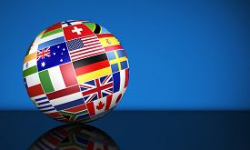 stock photo of flags world  - Travel services education and international business management concept with a globe and international flags of the world on blue background with copy space - JPG