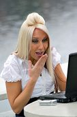 stock photo of smut  - A beautiful young blonde woman is shocked by what she is seeing on her laptop screen. It looks as if she is possibly seeing something offensive. ** Note: Slight blurriness, best at smaller sizes - JPG