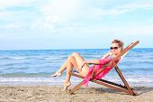 Lady sitting in chaise longue on the beach