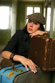 image of bitchy  - The beautiful woman in a cap sits with two suitcases - JPG