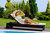 image of sunbathing woman  - Woman in a pool hat relaxing in a blue pool - JPG