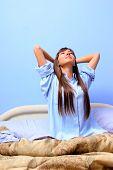 Постер, плакат: молодая женщина сидя в кровати и растянуть ее тело