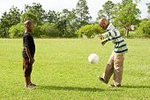 two african boys paly football in the park
