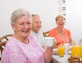 happy seniors friends having breakfast together