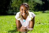 young african american woman relaxing on grass after doing fitness workout