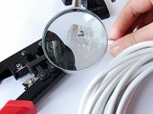 Hands Cheking The Network Cable (Cat5E) Under A Magnifier& Crimper Is Under It.