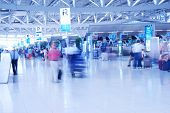 People in airport. Blurred. No recognizable faces or brandnames.