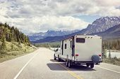 Caravan or recreational vehicle motor home trailer on a mountain road in Canada poster