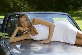 Blonde Model In White Dress Posing With A Convertible