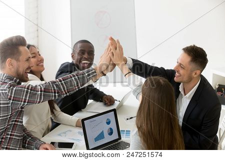 poster of Excited Diverse Millennial Group Giving High Five Celebrating Online Business Win Or Shared Goal Ach