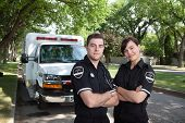 Portrait of two paramedics standing in front of ambulance vehicle
