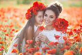 Mother And Daughter Into A Field Of Poppies.beautiful Mother And Her Daughter Playing In Spring Flow poster