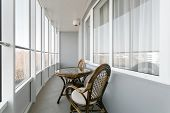 Glass Table And Rattan Wicker Seat Chair. Wicker Furniture Rattan Table Two Chairs Near The Window O poster