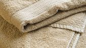 Beige Bath Towel. Folded Towel Texture. Bathroom Accessories Background poster