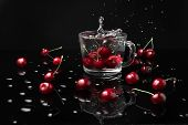 Macro Photo Of A Clear Glass Mug With Cherries In Front Of A Black Background On A Black Table Made  poster