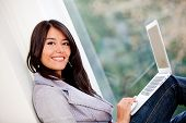 Woman managing her online business at home and smiling