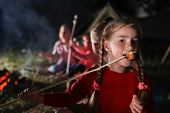 Adorable Little Girl With Roasted Marshmallow Near Bonfire At Night. Summer Camp poster