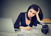 Young Woman Overwhelmed With Work Looking Stressed While Sitting At Table In Office. poster