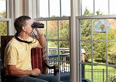 Man Watching Bird On Feeder