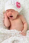 Newborn baby girl yawning.