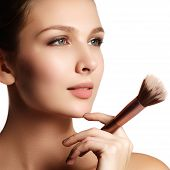 Beauty Model With Makeup Brush. Bright Make-up For Brunette Woman With Blue Eyes. Beautiful Face. Pe poster