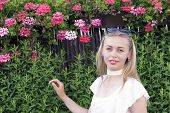 Portrait Of Beautiful Stylish Young Woman Posing Outdoors. Cute Blonde Standing Surrounded By Flower poster
