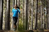 Woman running in wooded forest area, training and exercising for trail run marathon endurance. Fitness healthy lifestyle concept.