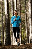 Woman running in wooded forest area, training and exercising for trail run marathon endurance. Fitne