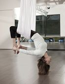 Woman doing anti gravity yoga exercise in fitness center.