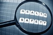 stock photo of workplace safety  - Focus on health and safety concept with magnifying glass and key words - JPG