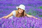Pretty woman lying down on lavender field, beautiful happy female sitting on purple flowers meadow,