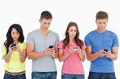 eine Gruppe von Menschen mit ihren Handys und Texte senden, da sie nebeneinander stehen