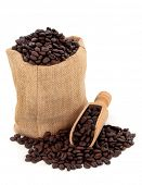 Coffee beans in a hessian sack and scoop over white background.