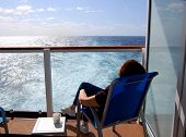 Relaxing Passenger On Stateroom Balcony Aboard Ship On Transatlantic Crossing