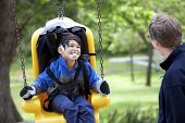 stock photo of babysitting  - Father pushing disabled son on yellow handicap swing - JPG