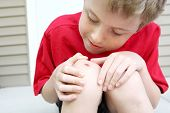 stock photo of scabs  - Boy with a scraped knee - JPG
