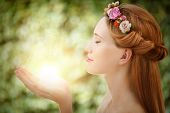 stock photo of nymphs  - Beautiful fairy woman with glow in hands on natural green background - JPG