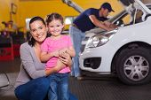 picture of auto garage  - happy young mother and little daughter in garage waiting their car to be serviced - JPG