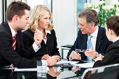 Business - meeting in an office, the businesspeople are discussing a document